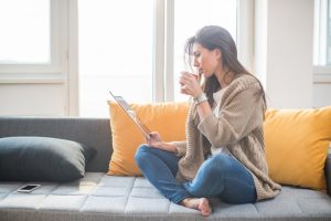Young woman sitting on the sofa drinking coffee and working on the digital tablet