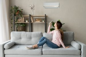 woman-with-remote-turning-on-ductless-air-handler-in-her-living-room